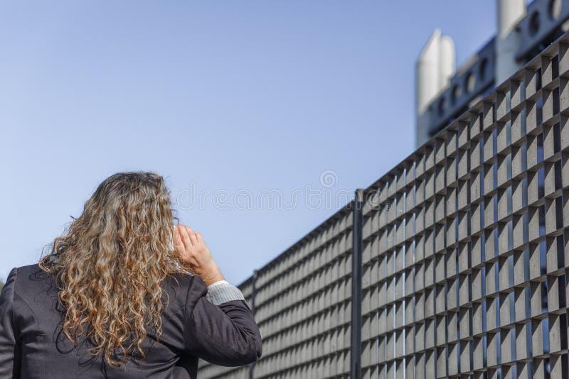 La femme blonde avec la veste foncée, va parler avec son téléphone portable photographie stock libre de droits