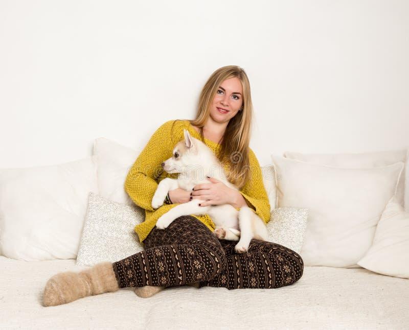La femme blonde dans des pyjamas et des chaussettes de laine avec le chiot enroué se trouve sur un lit blanc photographie stock libre de droits