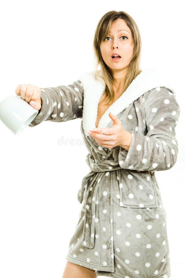 La femme blonde dans la robe de chambre grise avec des points montrent la tasse vide - non images stock