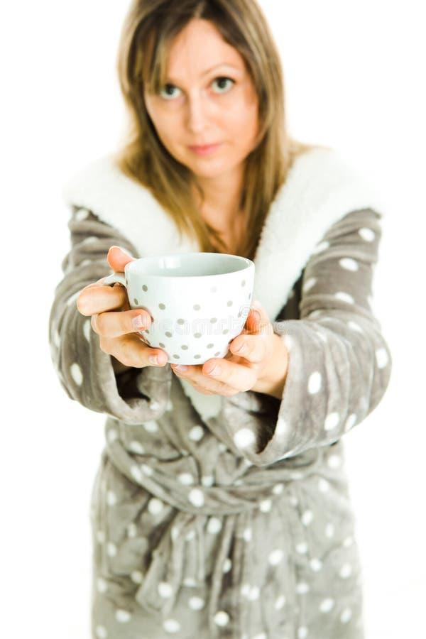 La femme blonde dans la robe de chambre grise avec les points blancs offre la tasse blanche avec les points gris photographie stock libre de droits