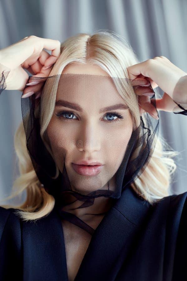 La femme blonde dans un manteau noir d'automne et un voile sur son visage se tient près d'une grande fenêtre Vêtements de mode d' photo libre de droits