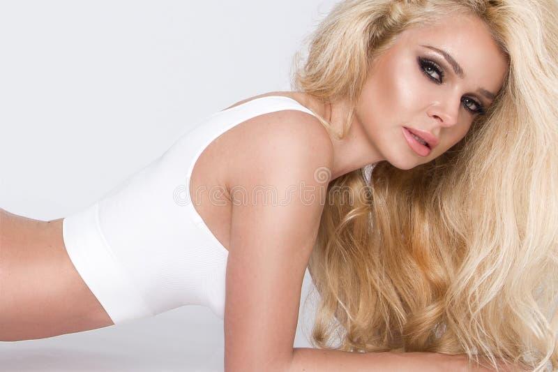 La femme blonde de belle jeune fille sportive s'est habillée dans le vêtement de sports tenant et jouant le football, ballon de f photo stock