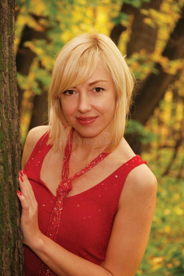 La femme blonde en rouge est par un arbre photo libre de droits