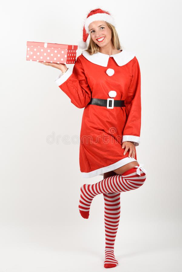La femme blonde en Santa Claus vêtx le sourire avec des boîte-cadeau photos stock