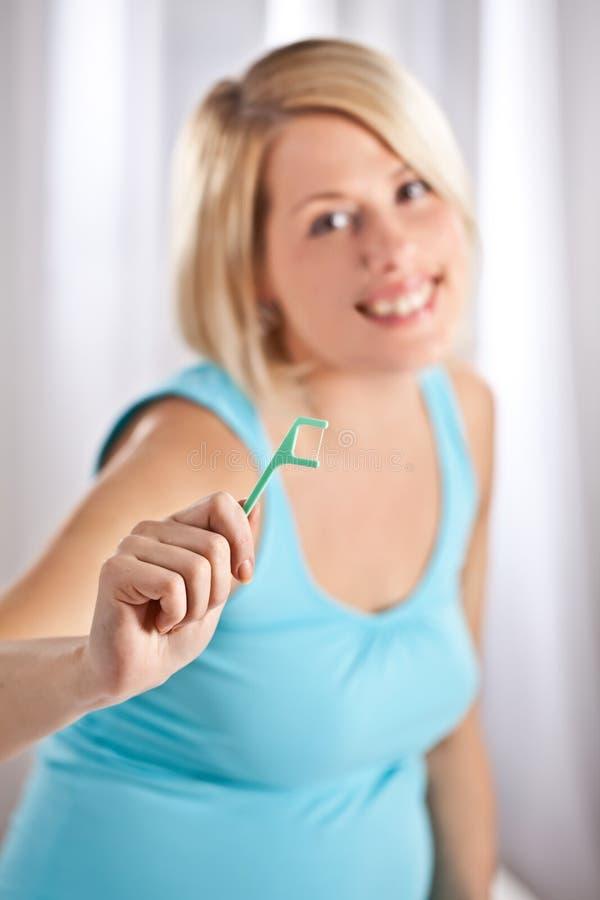 La femme blonde enceinte de positif contrôle ses dents photo stock