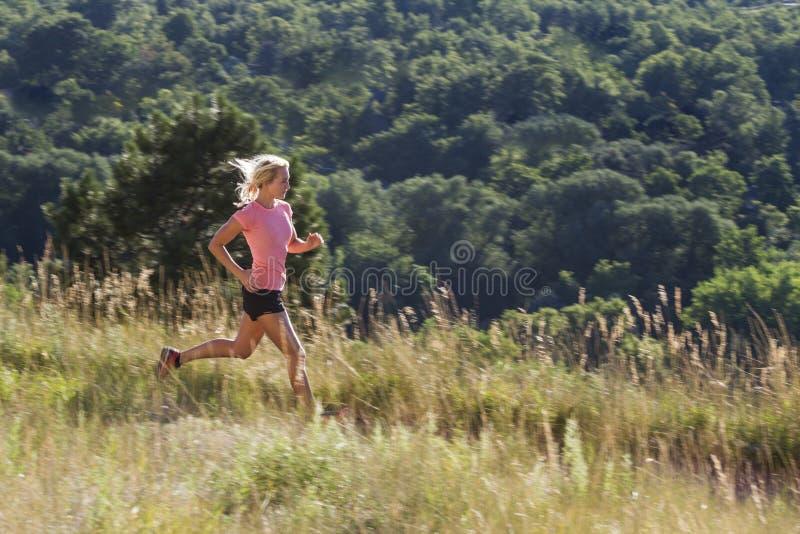 La femme blonde le début de la matinée courent avec le fond éloigné d'arbre images stock