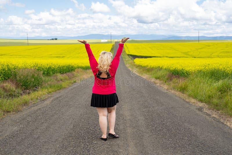La femme blonde pose sur un chemin d'exploitation vide avec des bras augmentés, près d'un champ des fleurs de moutarde dans la ré image stock
