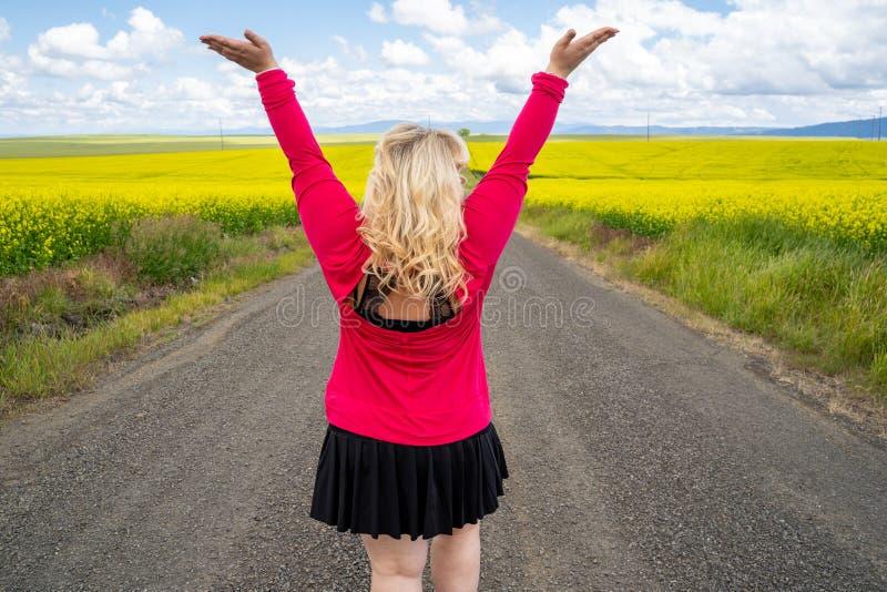 La femme blonde pose sur un chemin d'exploitation vide avec des bras augmentés, près d'un champ des fleurs de moutarde dans la ré photos stock