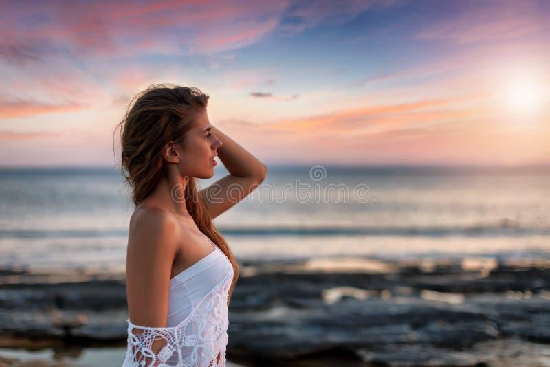 La femme blonde regarde le coucher du soleil fixement méditerranéen la plage photo libre de droits