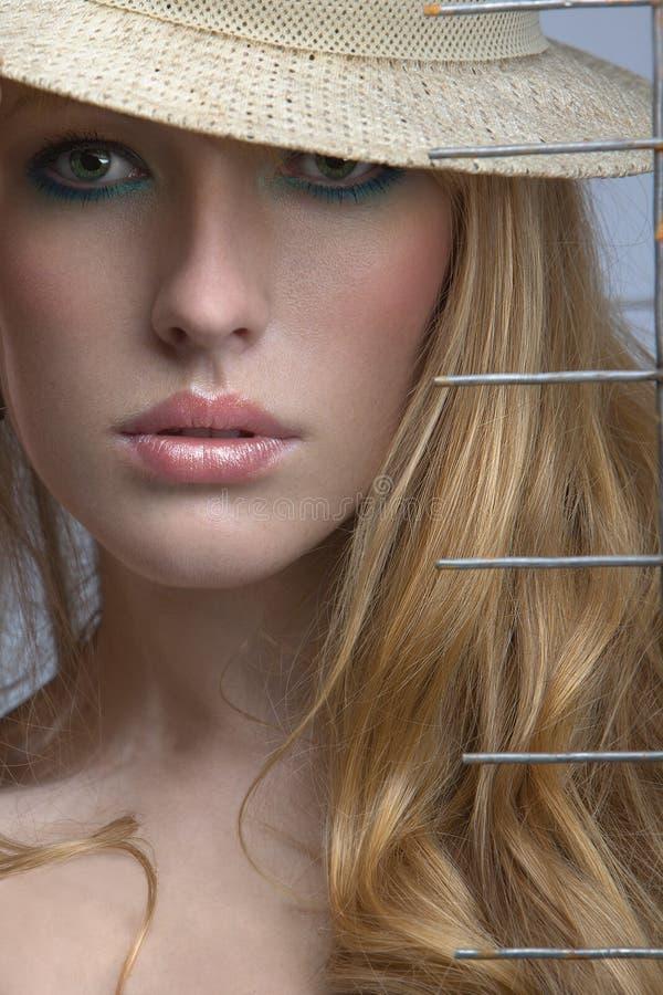 la femme blonde scrute à l'extérieur de dessous le Br photographie stock