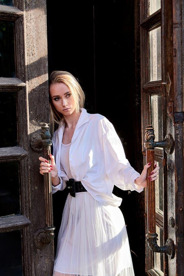 La femme blonde se tient dans la vieille porte en bois La vieille trappe en bois Portrait moderne de jeune femme photographie stock