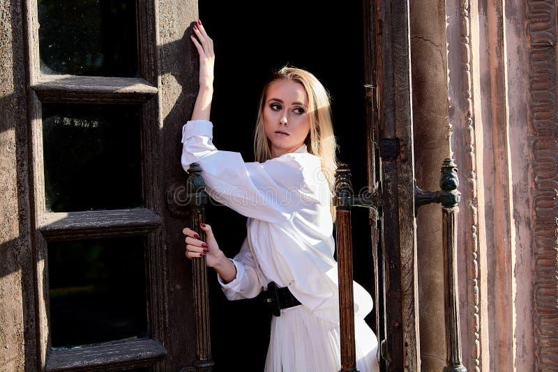 La femme blonde se tient dans la vieille porte en bois La vieille trappe en bois Portrait moderne de jeune femme photos libres de droits