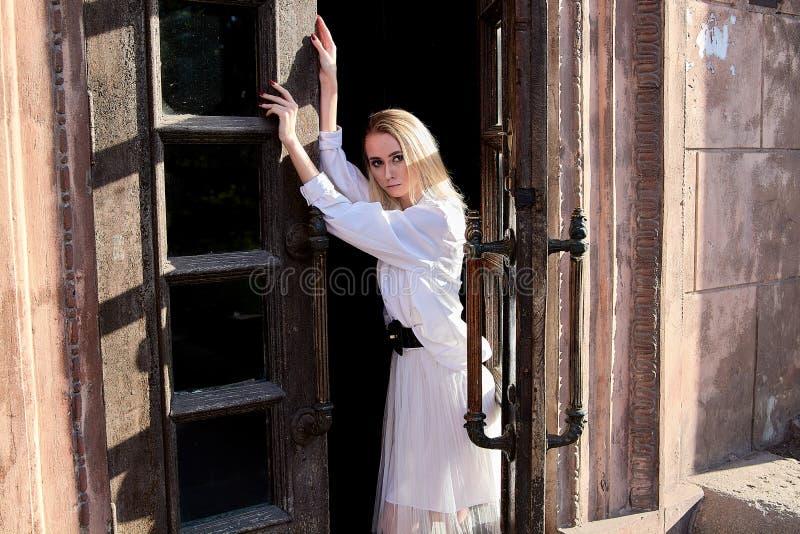 La femme blonde se tient dans la vieille porte en bois La vieille trappe en bois Portrait moderne de jeune femme image libre de droits