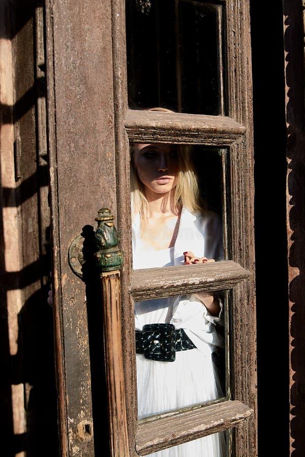 La femme blonde se tient dans la vieille porte en bois La vieille trappe en bois Portrait moderne de jeune femme photo stock