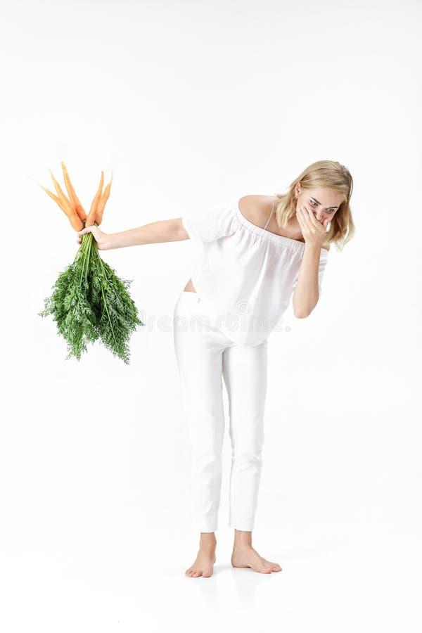 La femme blonde tenant la carotte avec le vert part sur le fond blanc la fille se sent mal des carottes et suit un régime images stock