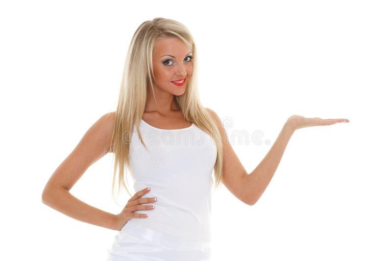 La femme blonde tient un objet imaginaire dans une main. photo stock