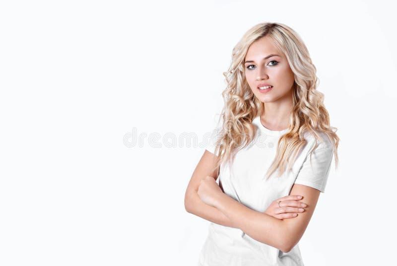 La femme blonde tient un objet imaginaire dans une main sur un fond blanc photo stock