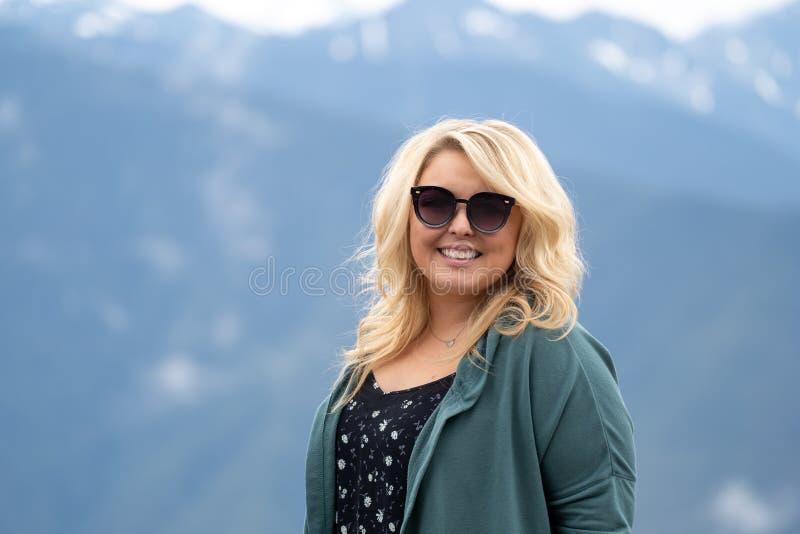 La femme blonde utilisant des lunettes de soleil pose pour un portrait avec les montagnes de cascade à l'arrière-plan image stock