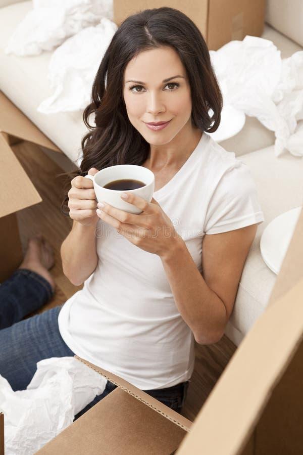 La femme boit du café éclatant des cadres déménageant la Chambre photos libres de droits