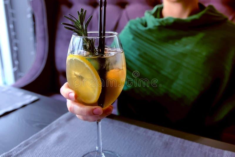 La femme boit le cocktail d'alcool en café Remet le plan rapproché images stock
