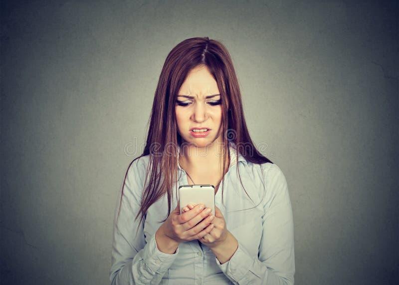 La femme bouleversée regardant le téléphone portable a contrarié avec le message qu'elle a reçu image libre de droits