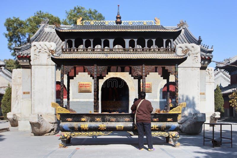 La femme brûle l'encens sur un autel au temple de Bai Yun Guan, Pékin, Chine photographie stock