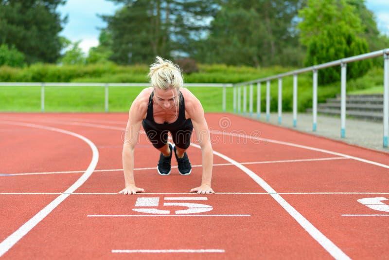 La femme célibataire étirant le veau muscles à la voie de course image stock