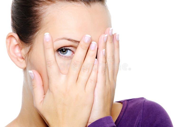 La femme cachent son visage et l'observent par des doigts photos stock