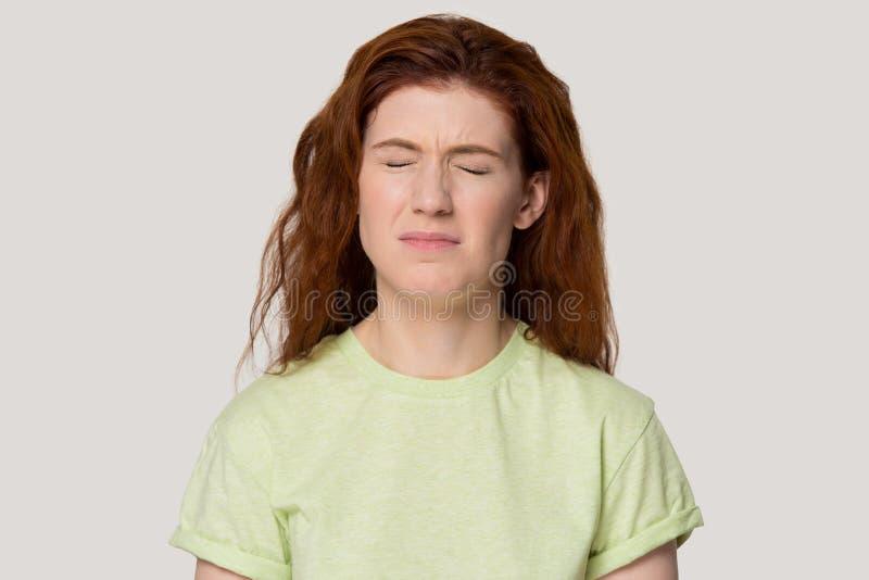 La femme capricieuse malheureuse rousse a fermé le headshot de froncement de sourcils de studio de sourcils de yeux photographie stock