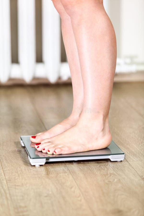 La femme caucasienne avec les pieds nus est sur des échelles de poids de plancher image libre de droits