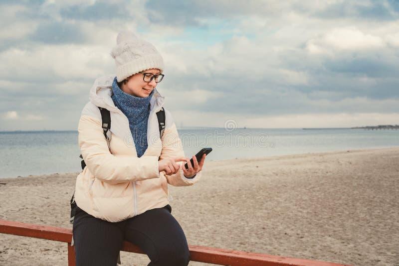 La femme caucasienne dans le chapeau et la veste avec un sac à dos en hiver s'assied sur une jetée en bois sur la plage près de l photos stock