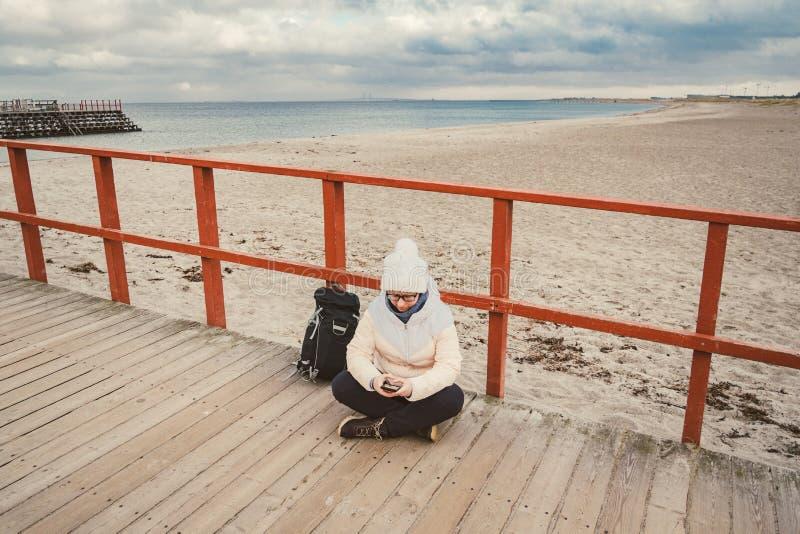 La femme caucasienne dans le chapeau et la veste avec un sac à dos en hiver s'assied sur une jetée en bois sur la plage près de l image stock