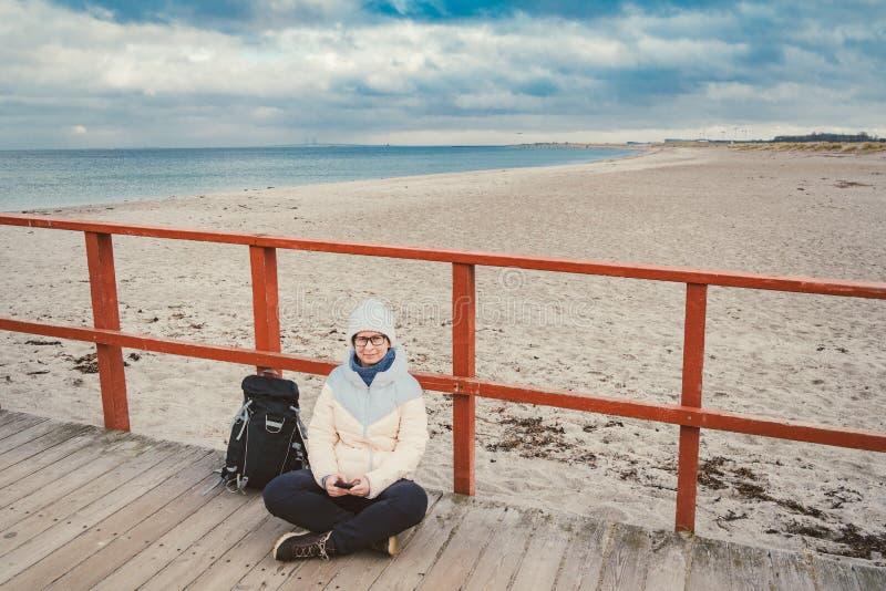 La femme caucasienne dans le chapeau et la veste avec un sac à dos en hiver s'assied sur une jetée en bois sur la plage près de l photographie stock