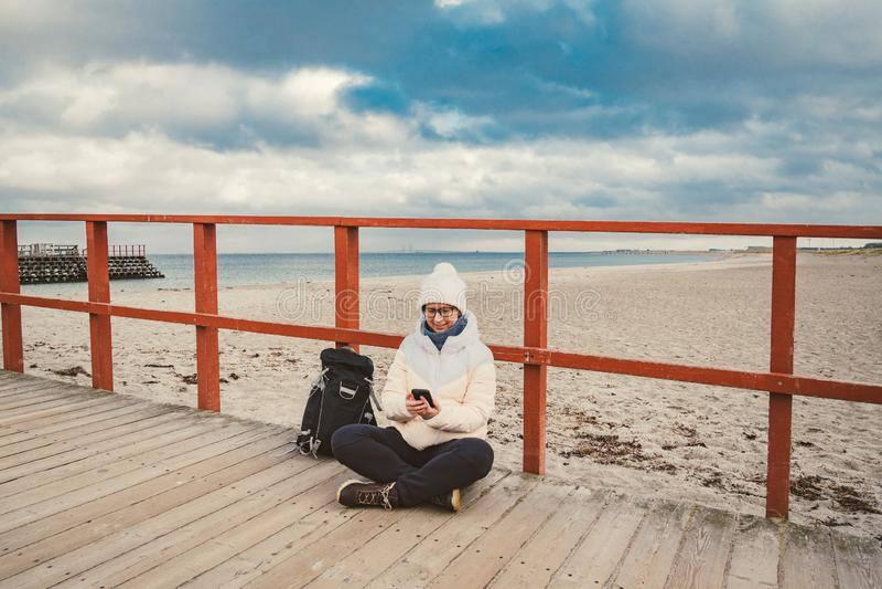 La femme caucasienne dans le chapeau et la veste avec un sac à dos en hiver s'assied sur une jetée en bois sur la plage près de l images stock
