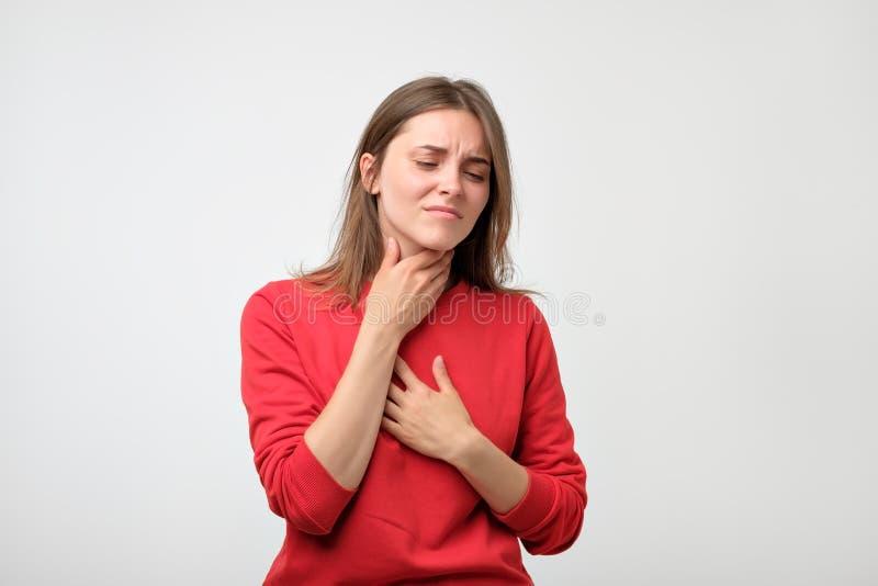La femme caucasienne malheureuse dans le pulover rouge souffrant de la gorge font souffrir à la maison photographie stock libre de droits