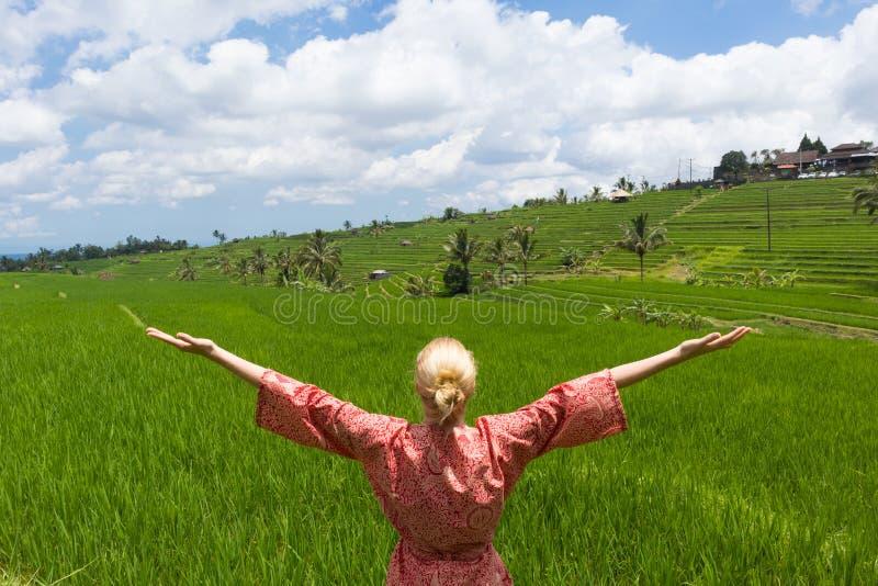 La femme caucasienne ? la mode d?tendue utilisant le kimono asiatique rouge de style, bras rised au ciel, appr?ciant la nature pu photo stock