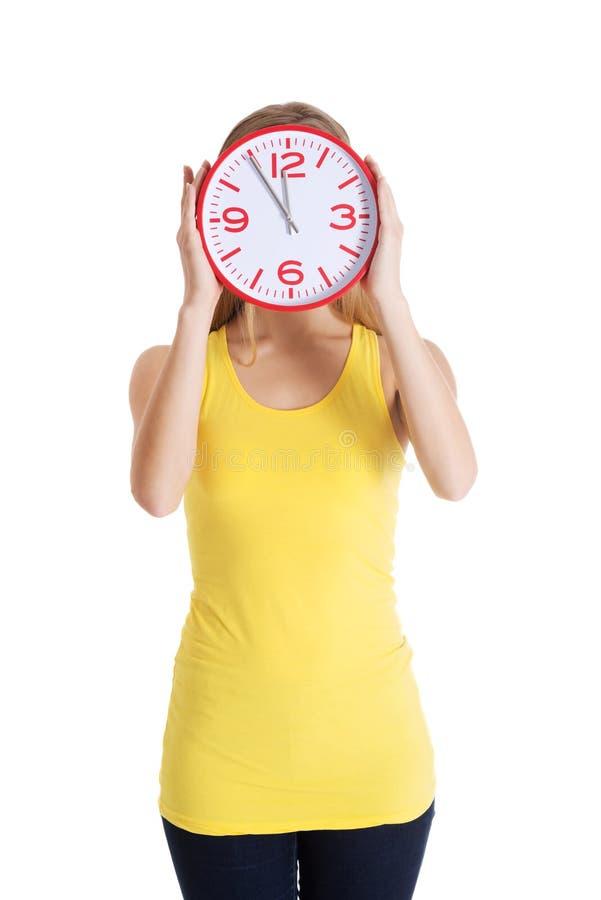 La femme caucasienne occasionnelle tient l'horloge sur son visage. photos stock