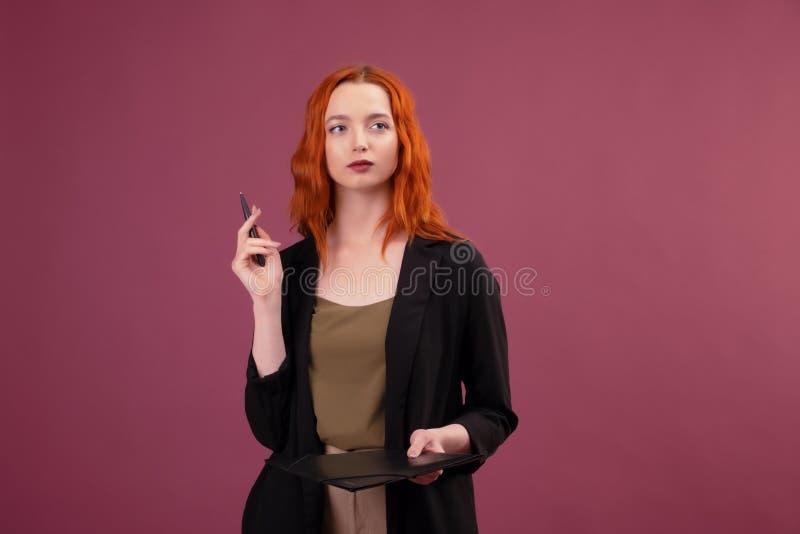 La femme caucasienne rousse mignonne se tient sur le fond rose tenant son dossier rouge de t?l?phone portable et de document image stock