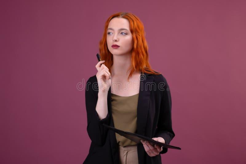 La femme caucasienne rousse mignonne se tient sur le fond rose tenant son dossier rouge de t?l?phone portable et de document photo stock