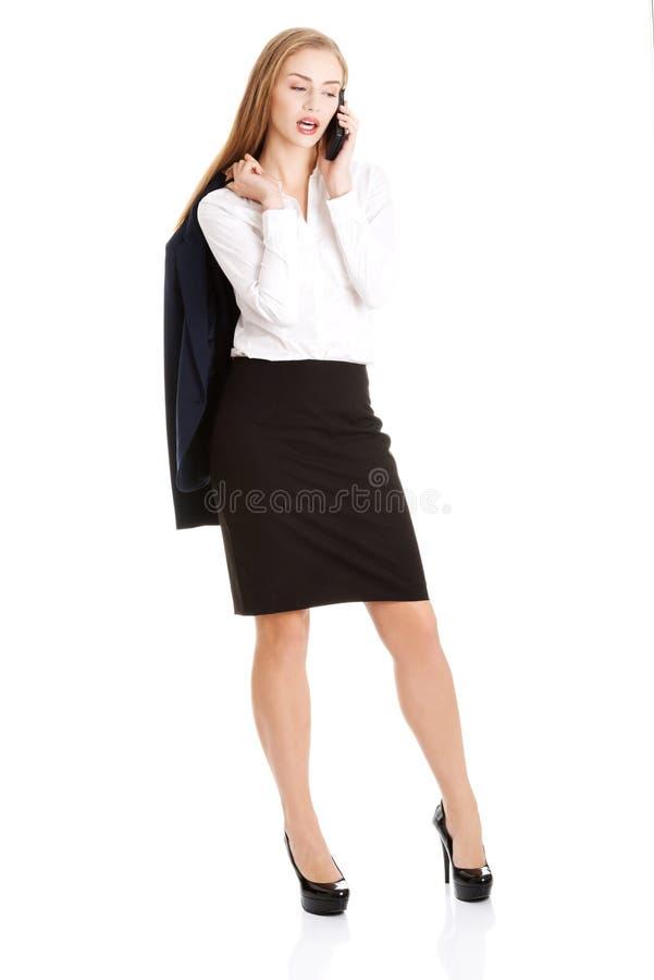 La femme caucasienne sensuelle attirante d'affaires parle par le téléphone photographie stock libre de droits