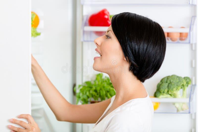 La femme cherche la nourriture dans le réfrigérateur ouvert photo libre de droits