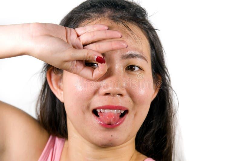 La femme chinoise asiatique heureuse et belle d'adolescent émulant des doigts nouent le geste de la célébration de but de joueur  photographie stock