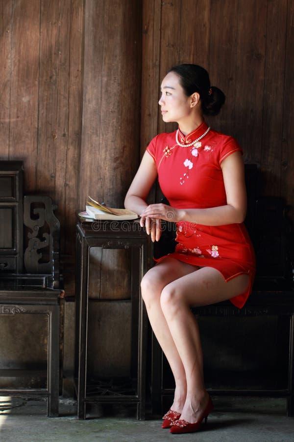 La femme chinoise heureuse dans le cheongsam rouge a lu le livre photographie stock