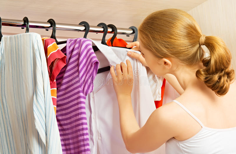 La femme choisit des vêtements dans le cabinet de garde-robe à la maison photos libres de droits