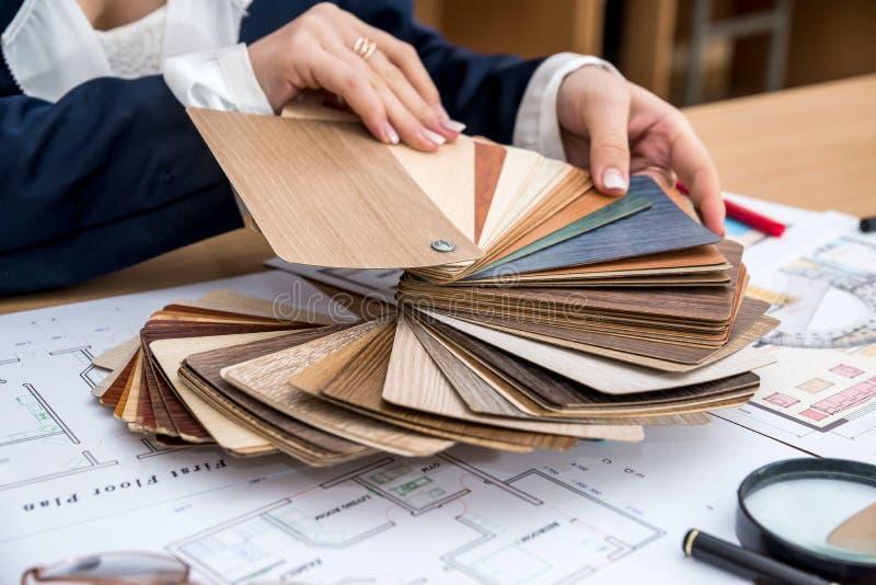 La femme choisit le matériel en bois de concepteur photos libres de droits