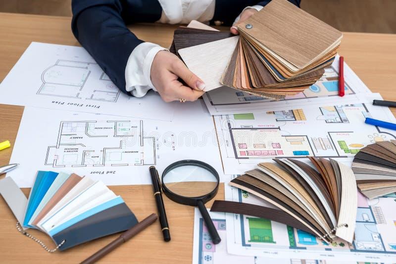 La femme choisit le matériel en bois de concepteur pour la maison moderne images libres de droits