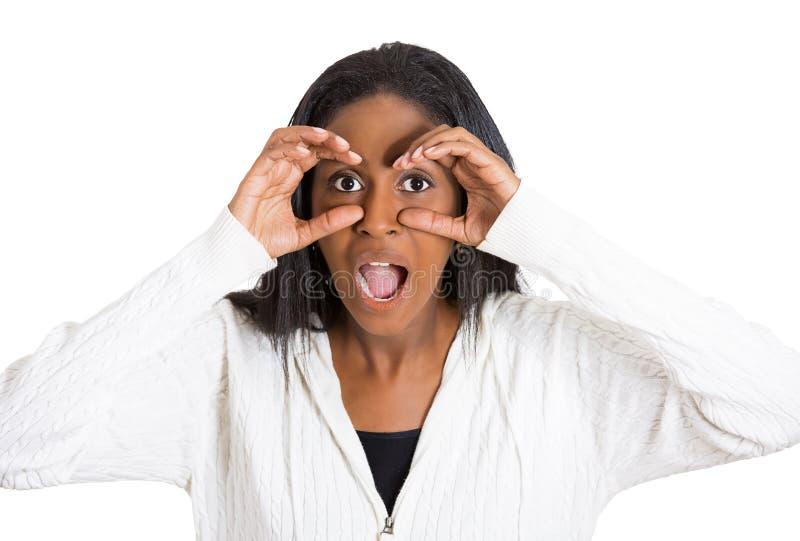 La femme choquée étonnée curieuse jetant un coup d'oeil, par des doigts aiment des jumelles image libre de droits