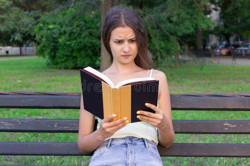 La femme choquée et étonnée tient un livre et a contrarié le regard photographie stock