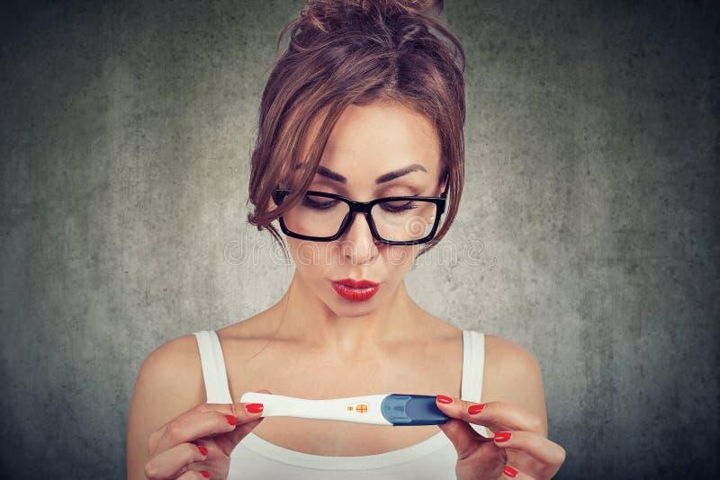La femme choquée ne peut pas croire ses yeux tout en vérifiant l'essai de grossesse positif image stock