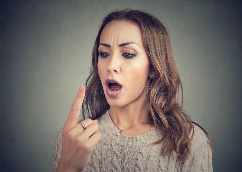 La femme choquée regardant son doigt a la double vision photo stock